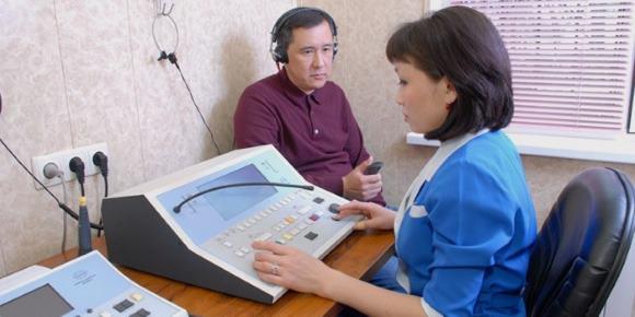 Сурдолог проводит обследование пациента с шумом в ушах