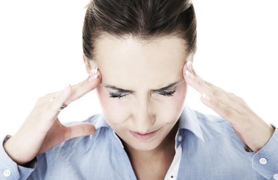 Женщина страдает головной болью