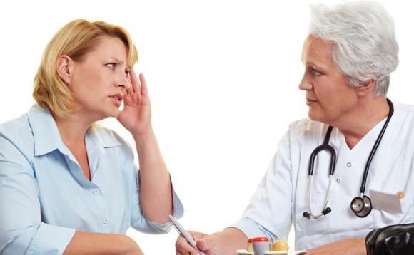 Женщина на приеме у врача по поводу мигрени