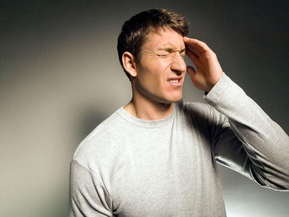 Молодой человек страдает от цефалгии