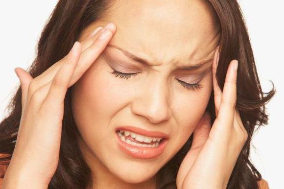 Женщина страдает от цефалгии в области висков и лба