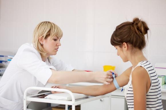 Девушка в процедурном кабинете сдает кровь на биохимический анализ
